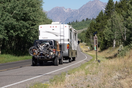 A camper on a highway heading toward the Tetons