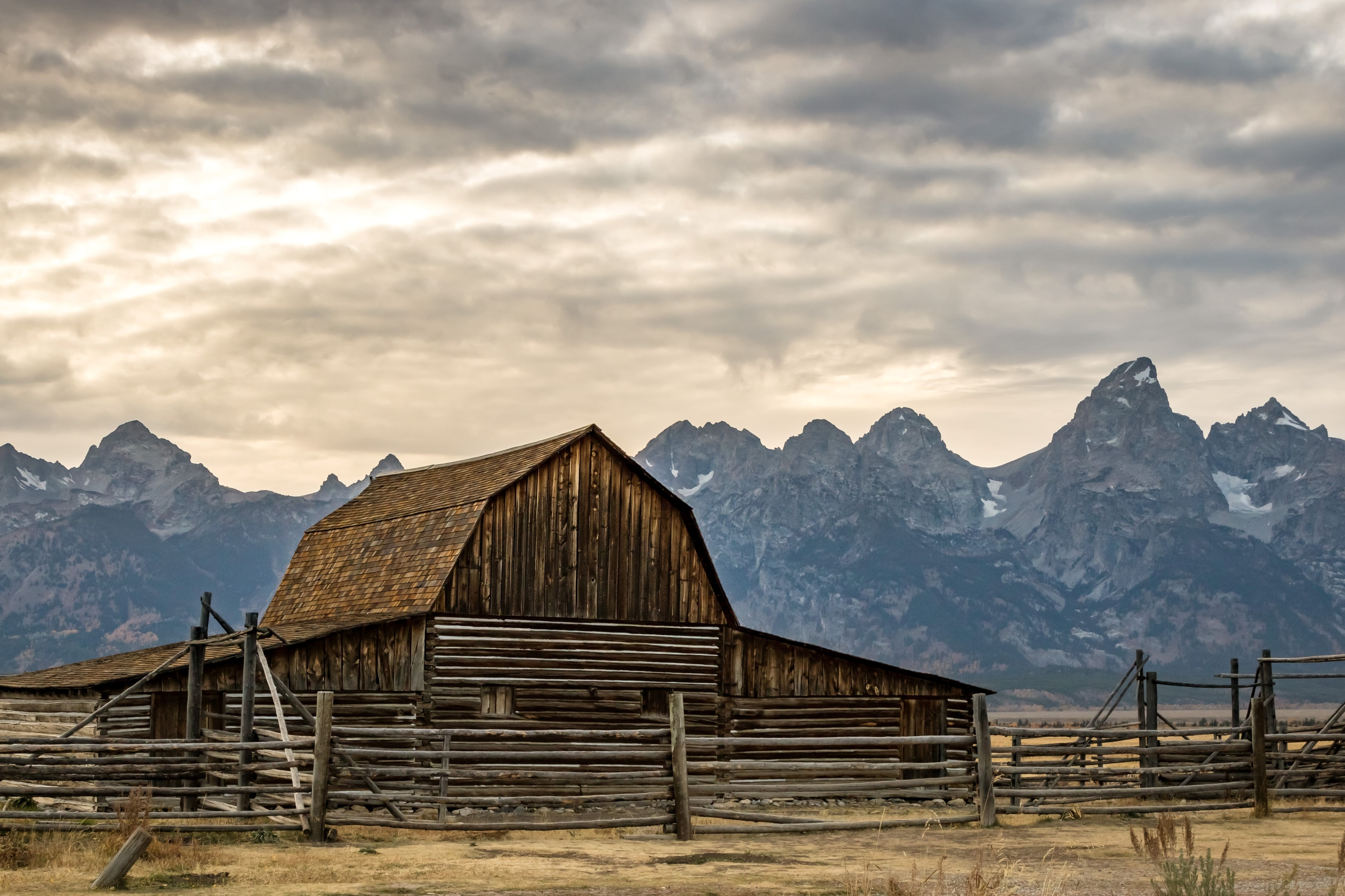 Barn in front of the Tetons on an overcast day.