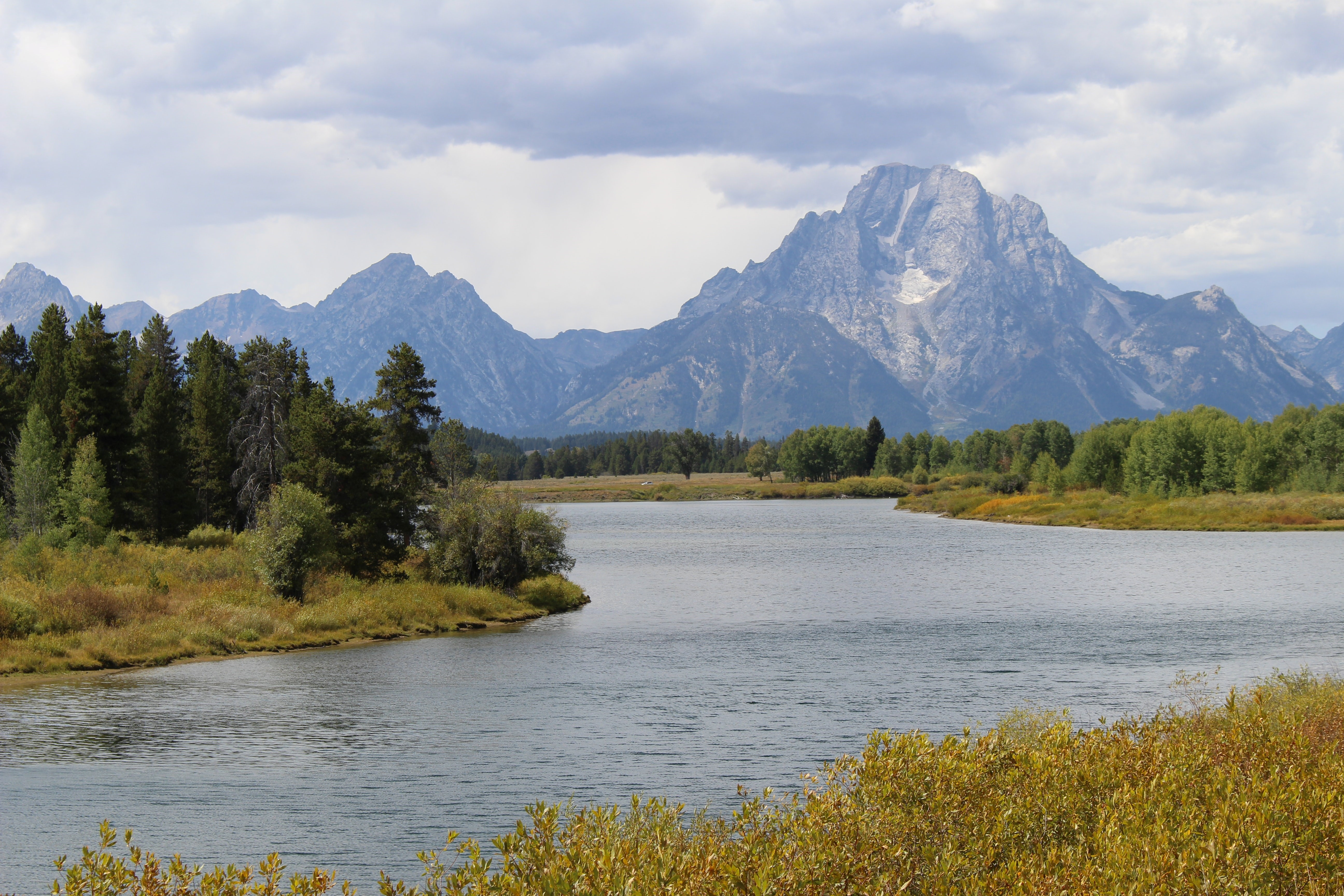 A view of the Snake River with the Tetons in the background on an overcast day.