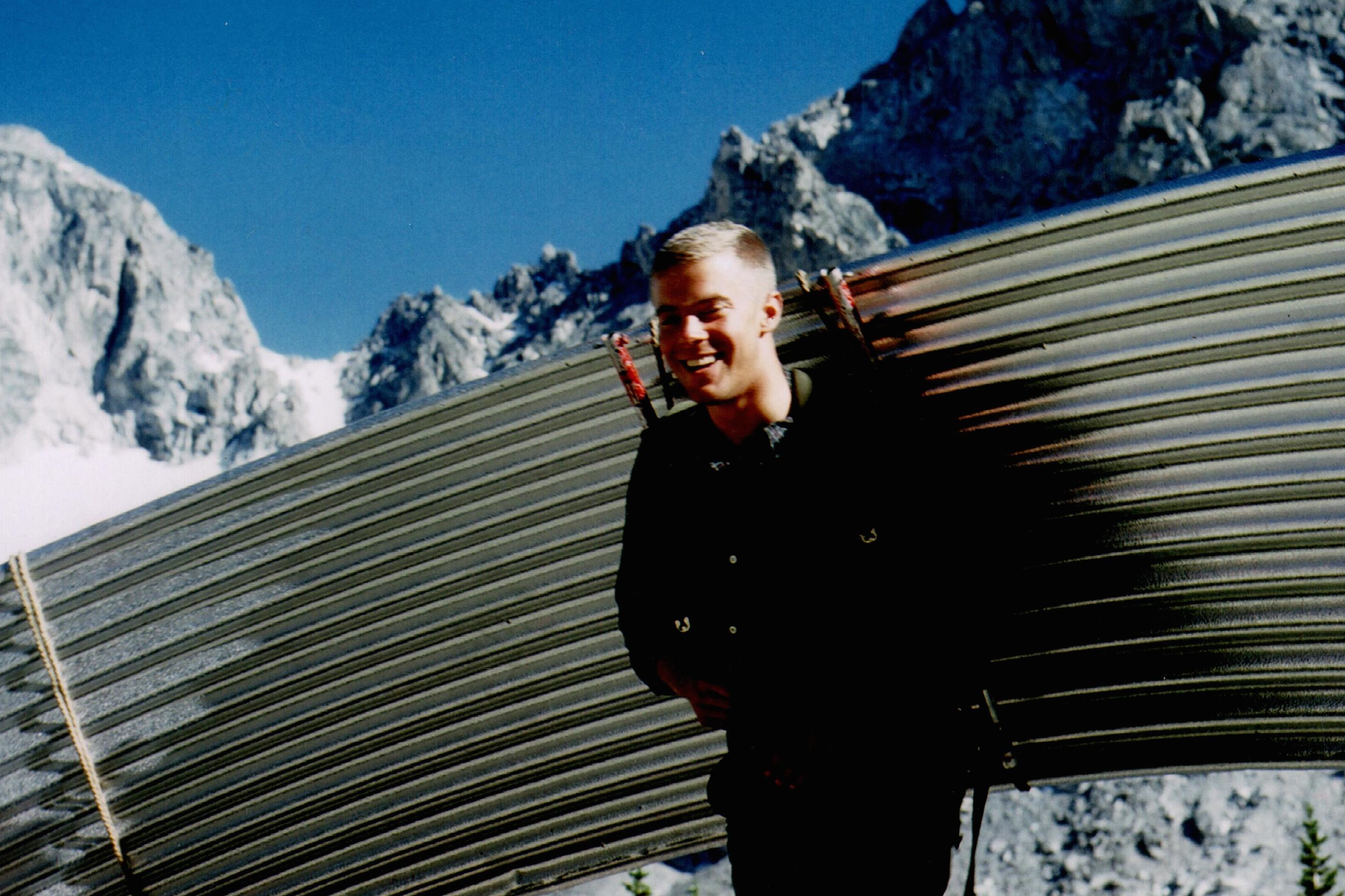 Man with a large sheet of metal strapped to his back with snowy, rocky mountains in the background