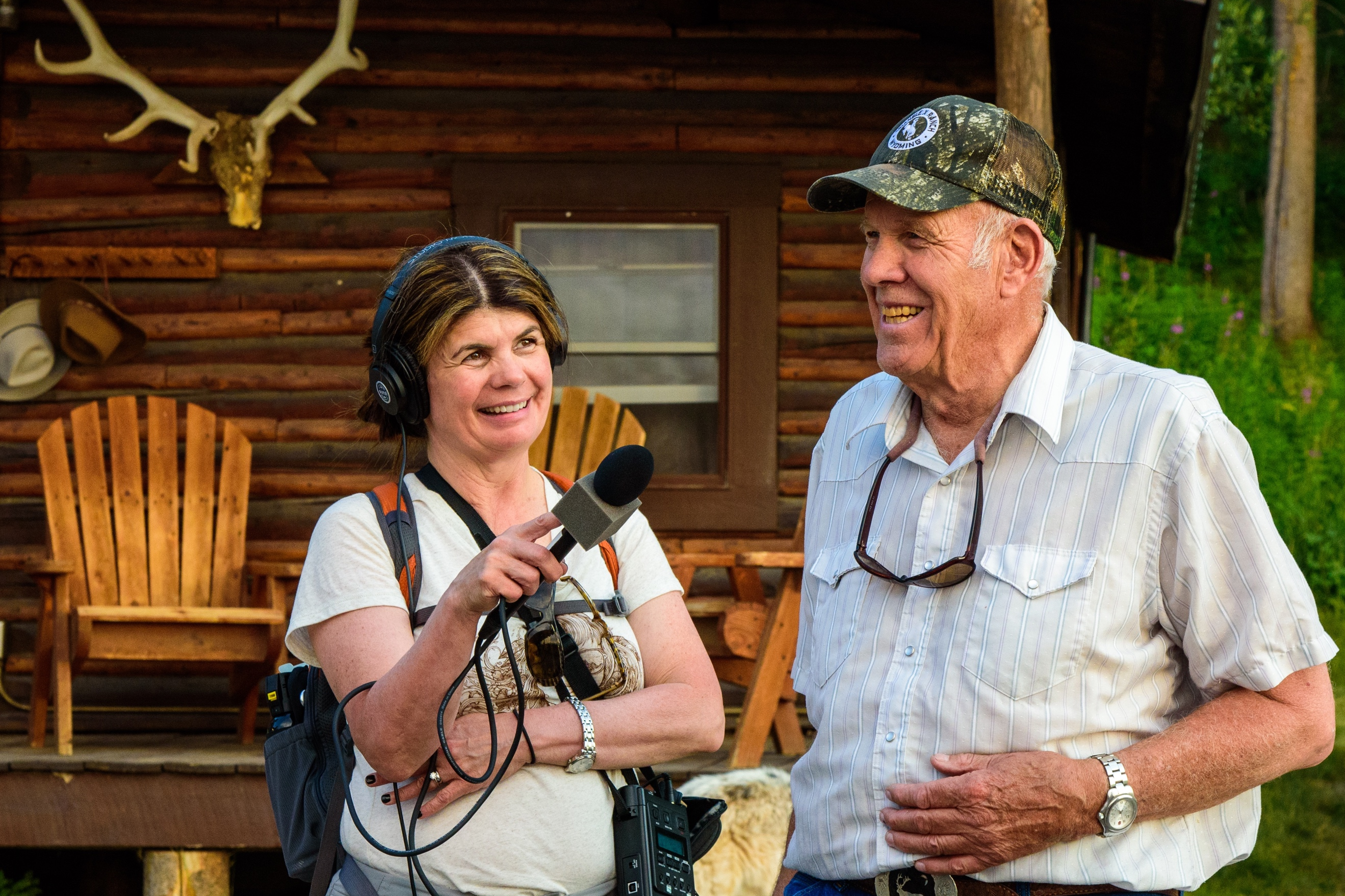A woman holding a microphone up to a man in front of a log cabin