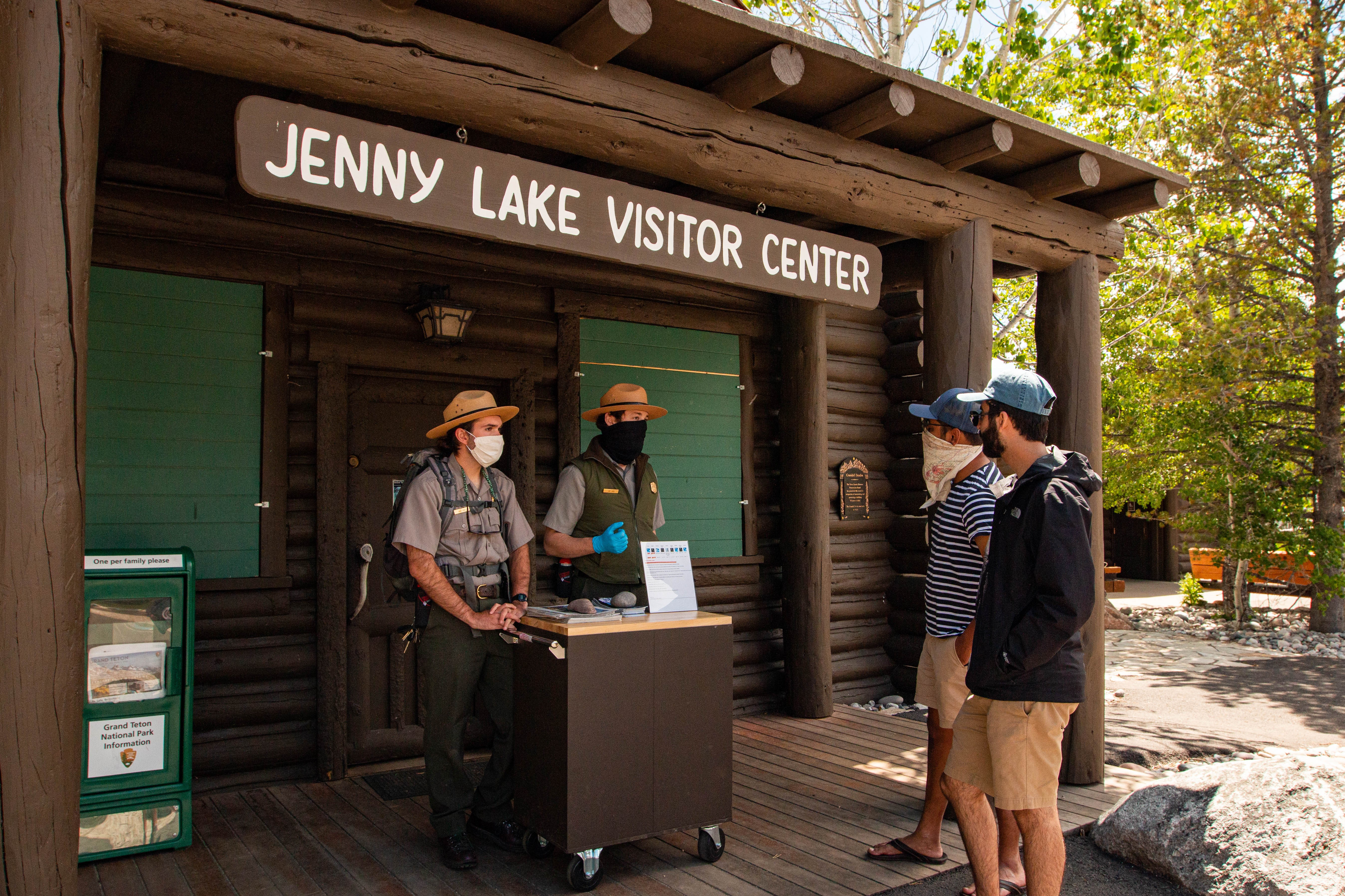 """Park rangers and visitors wearing masks talking on the porch of a building marked, """"Jenny Lake Visitor Center"""""""